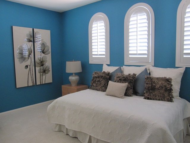 Blue bedroom with white plantation shutters.